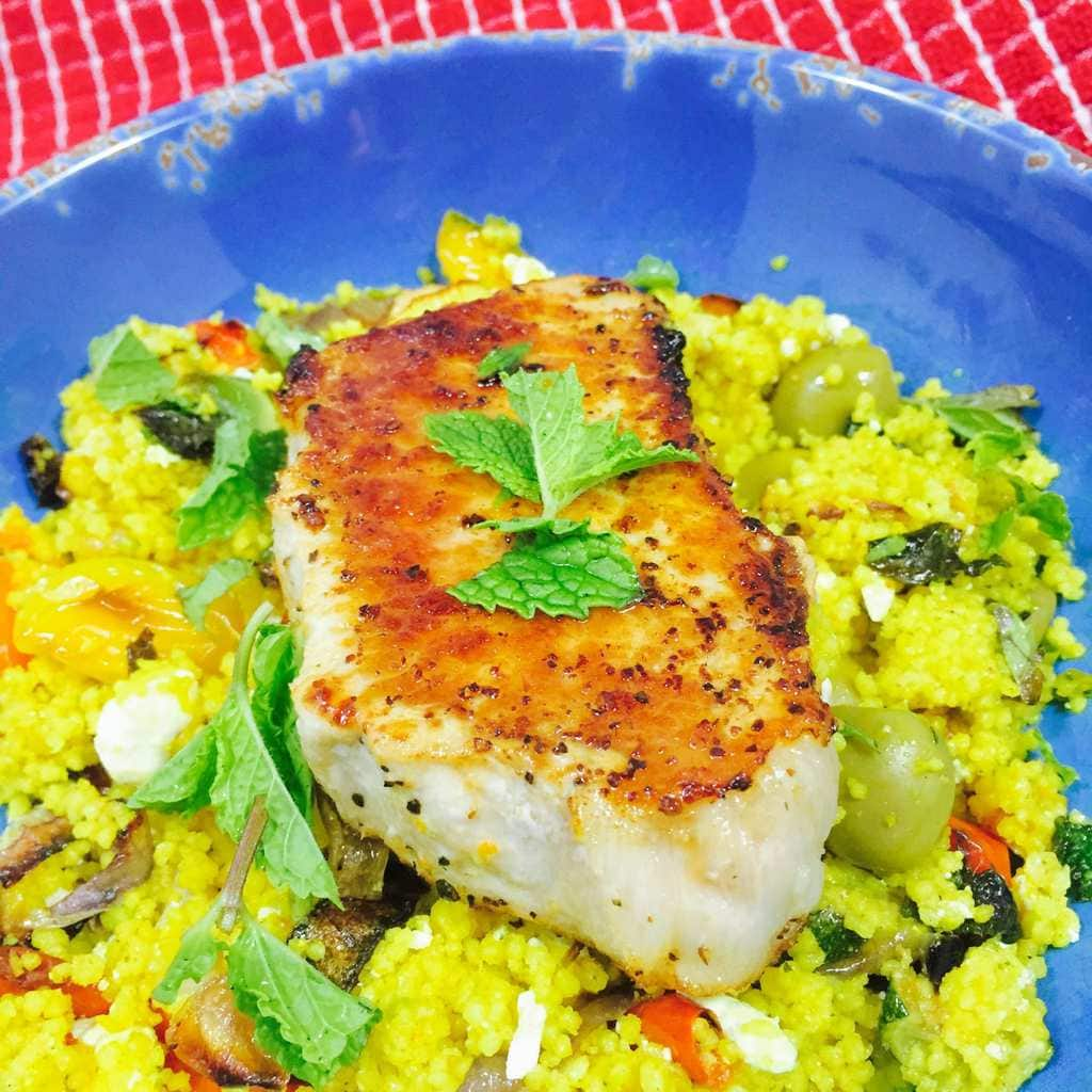 Baked pork chop resting on curry vegetable couscous on a blue plate.