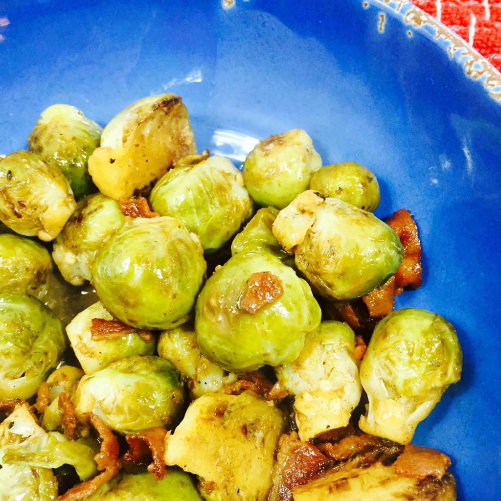 Cooked Brussels sprouts with bacon in a blue bowl