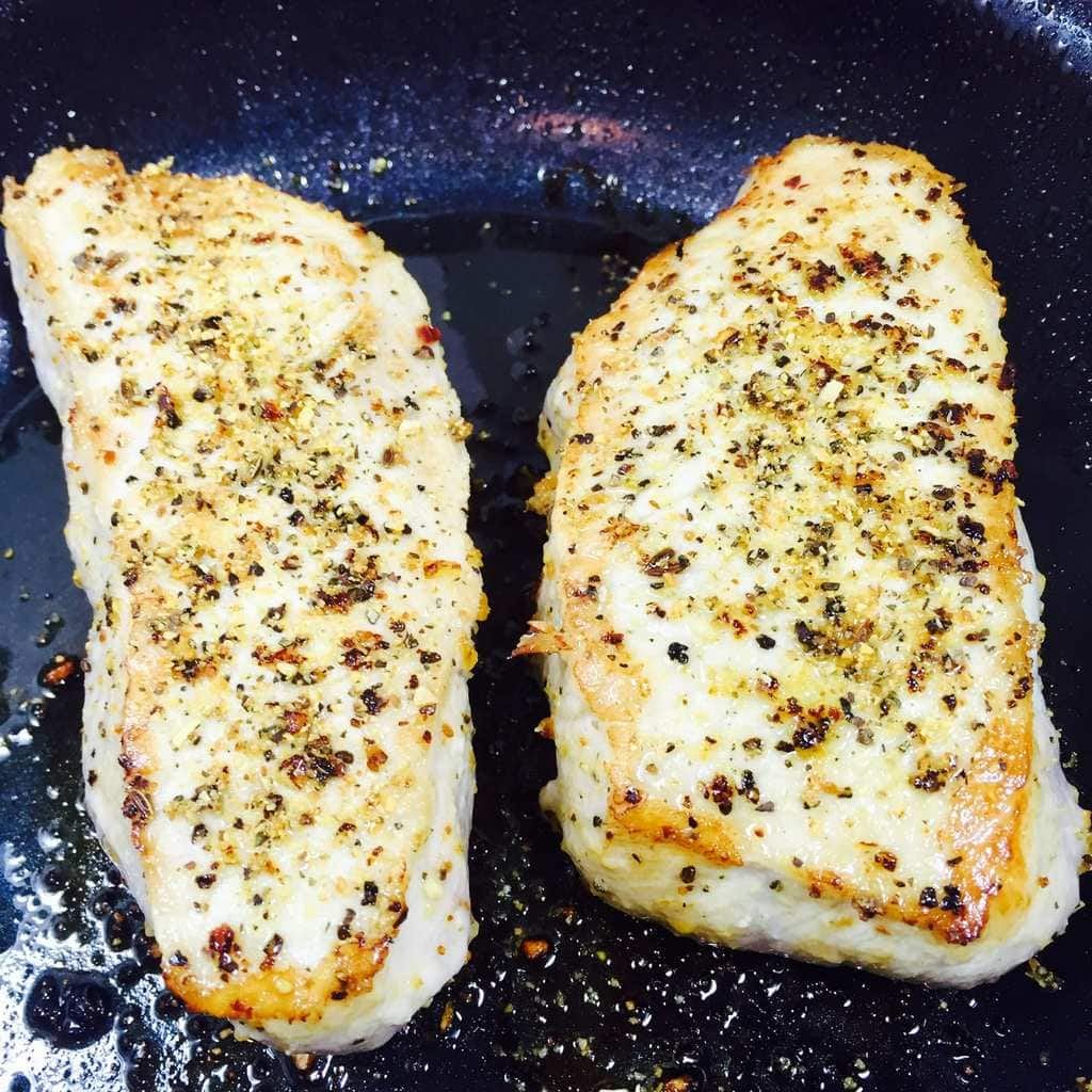Seared pork chops in pan