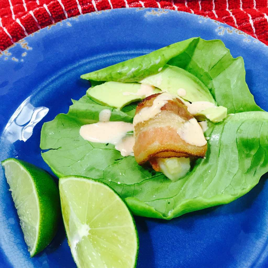 bacon wrapped scallop lettuce wrap on a blue plate