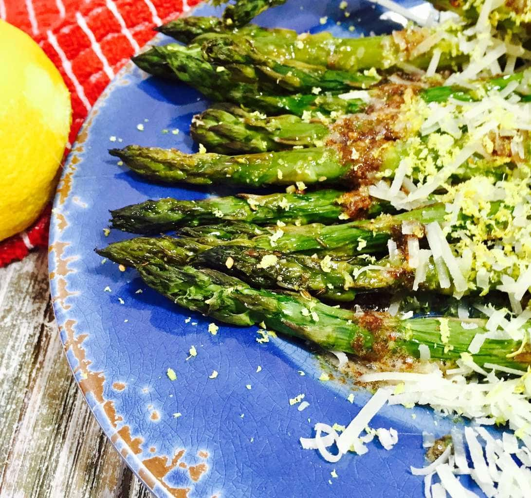 Cooked asparagus with browned butter on a blue plate