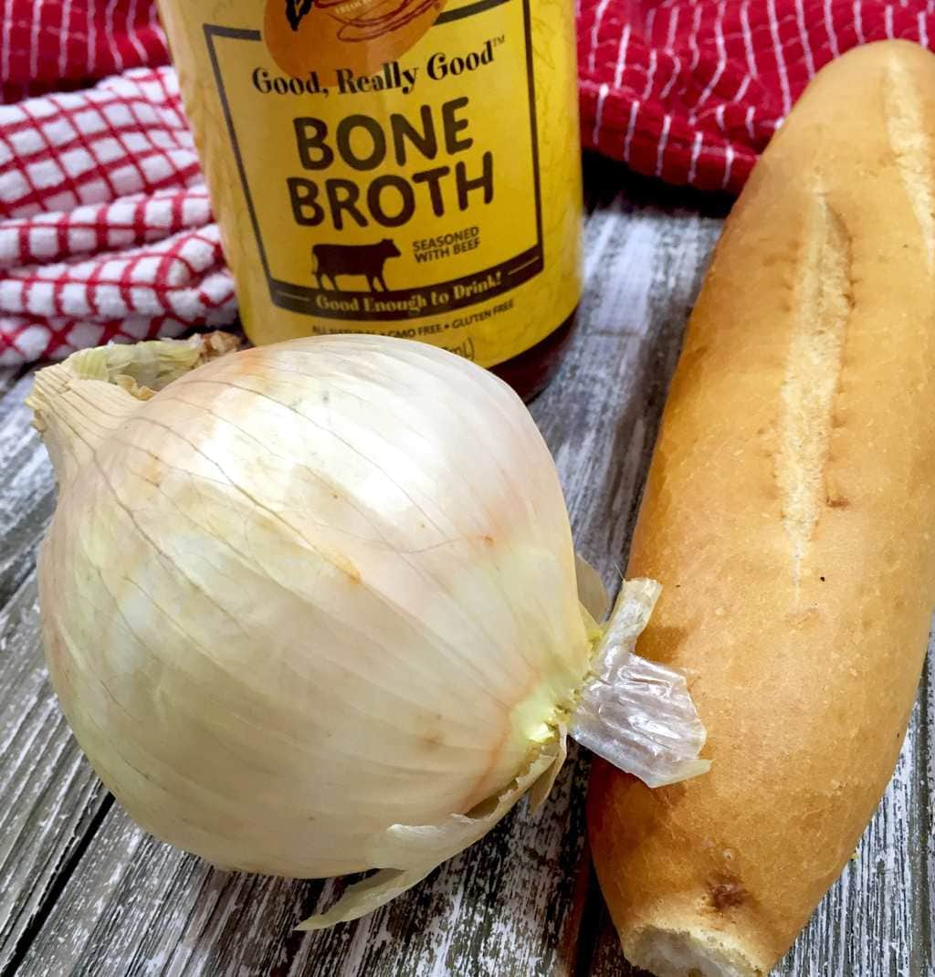 Yellow onion, Bone broth and French baguette on a wooden table