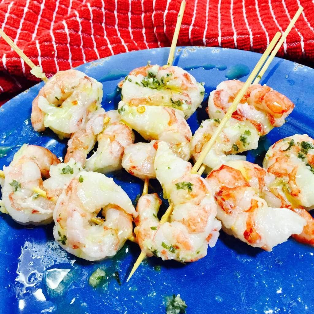 skewers shrimp on a blue plate