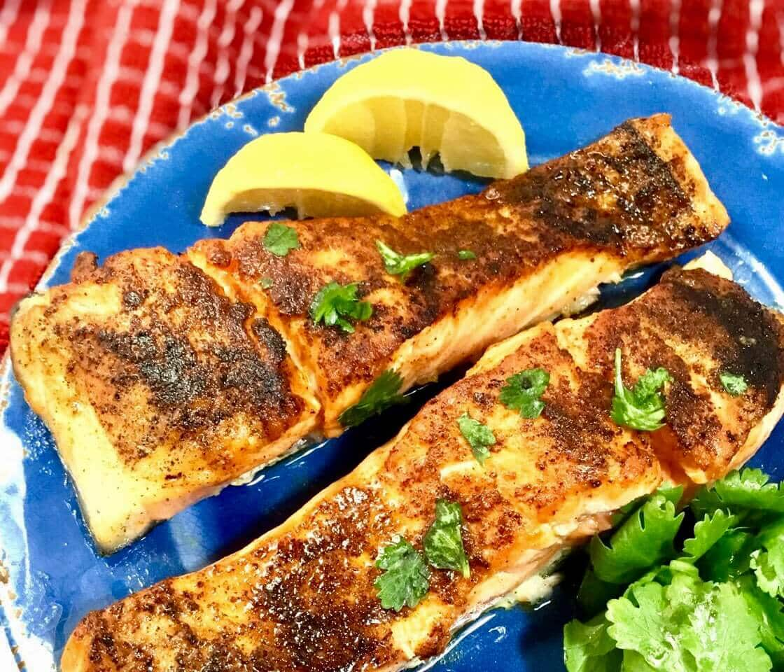 baked salmon on a blue plate with lemon