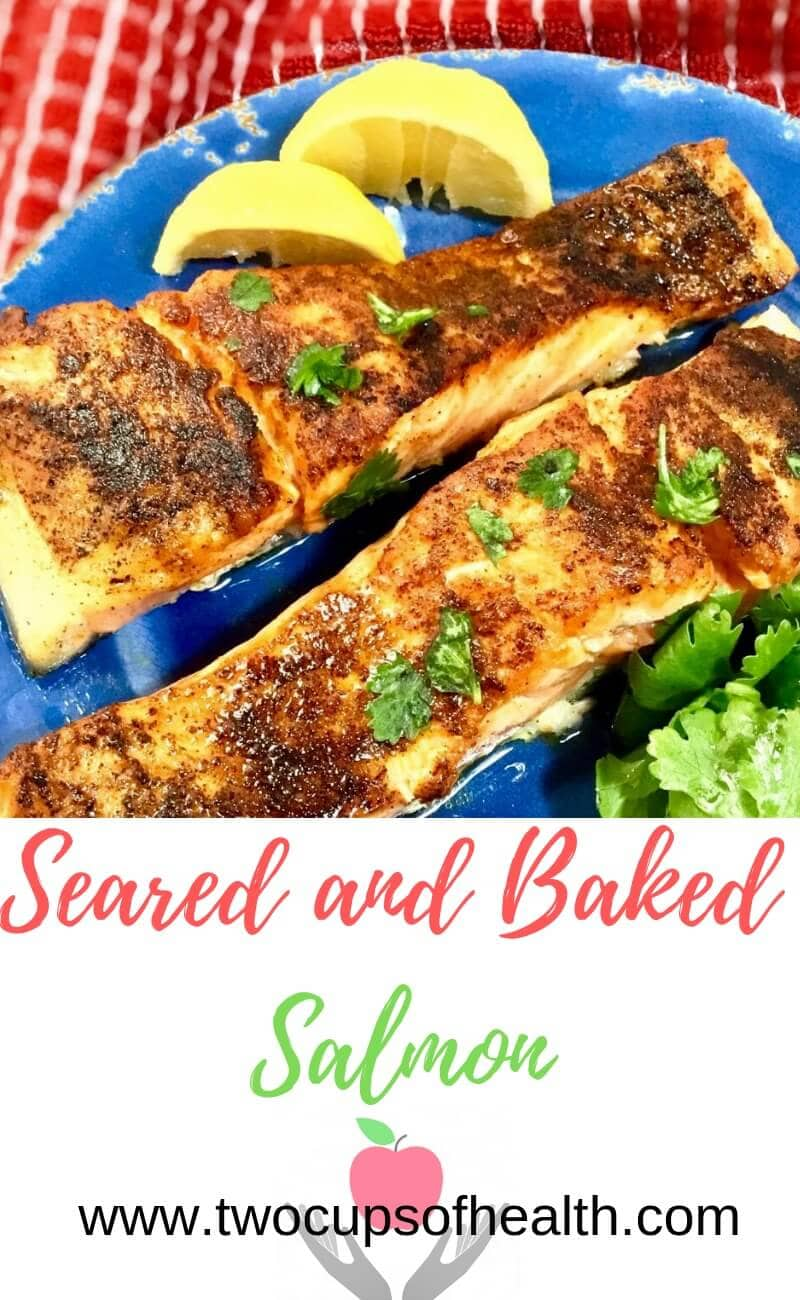 baked salmon on a blue plate with lemons and parsley