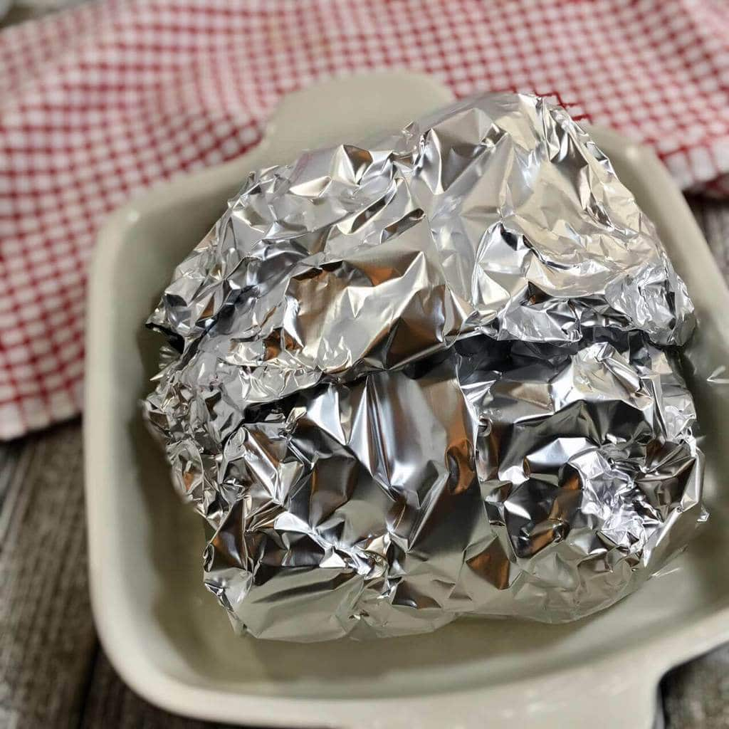 Brisket wrapped in foil in a white dish