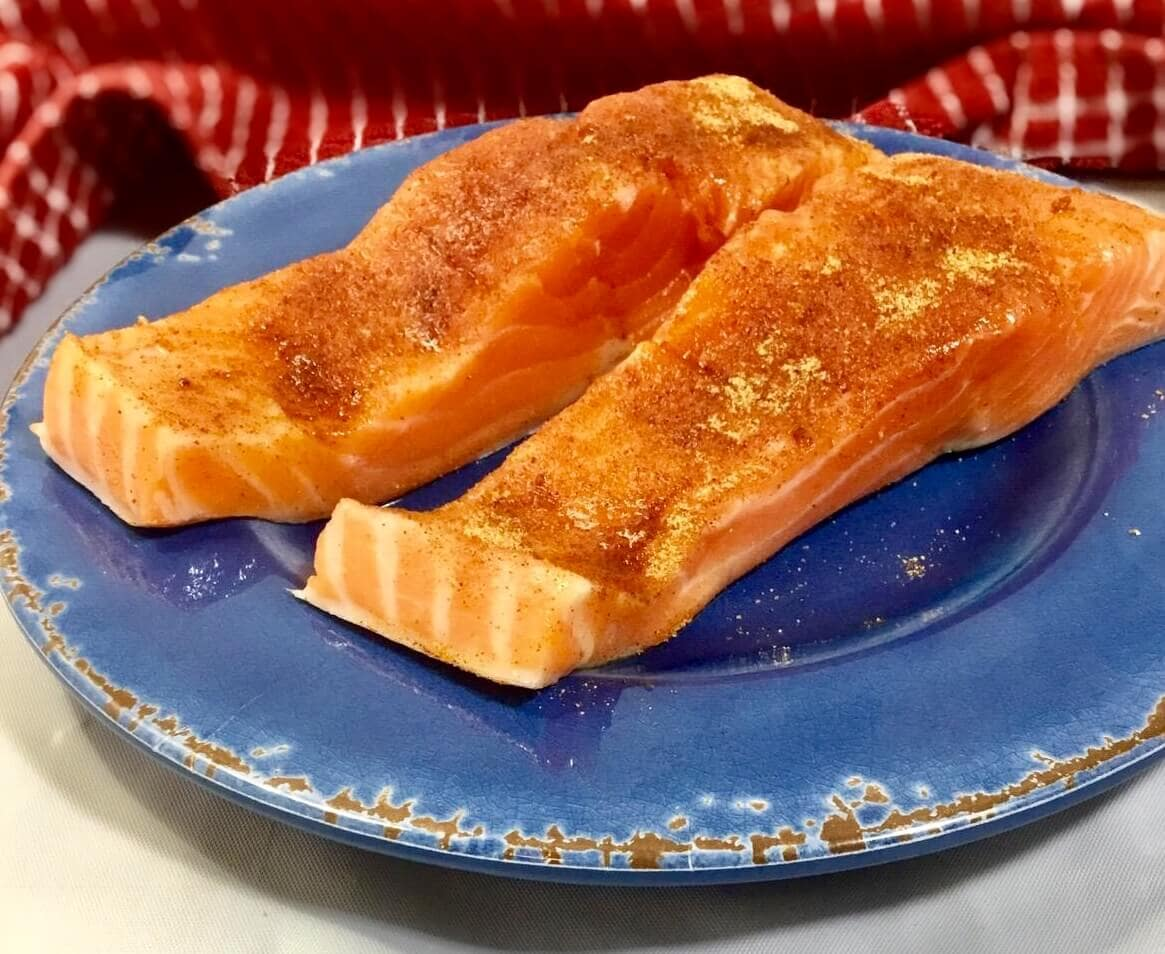 seasoned salmon on a blue plate ready to be baked